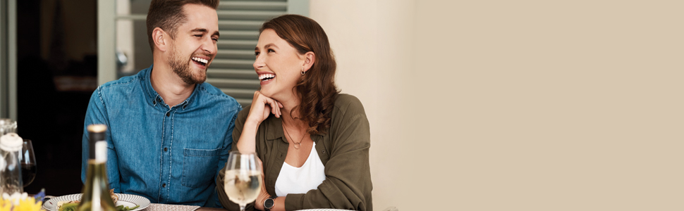 Happy smiling couple sit at a table enjoying a meal with a bottle of wine.