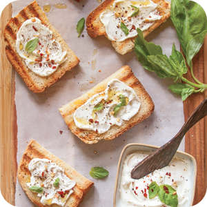 grilled toast on a cutting board covered with spread.