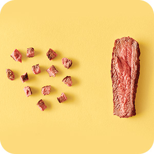 Image of beef cut into little bites, on yellow background.