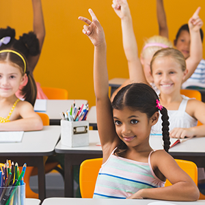 Children inside of a classroom raising their hands to participate