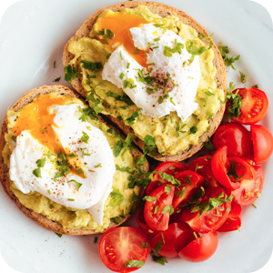 Image of avocado toast, with poached egg, tomato salad.